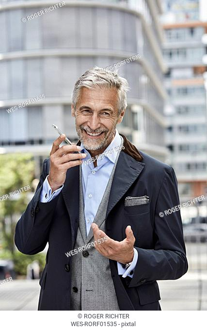 Germany, Duesseldorf, portrait of laughing mature businessman talking on mobile phone