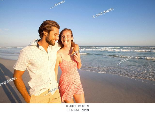 Smiling couple, man with arm round woman, walking along sunny beach