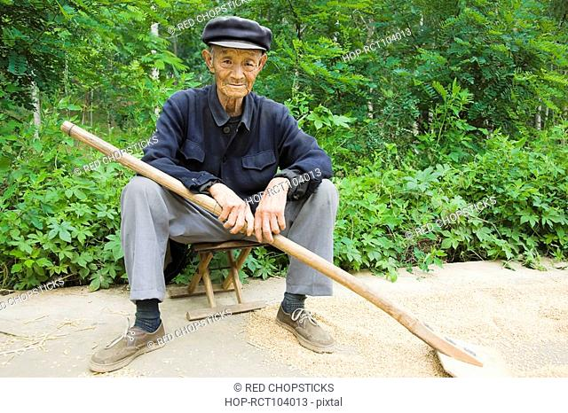 Portrait of a farmer sitting on a stool in a field, Zhigou, Shandong Province, China