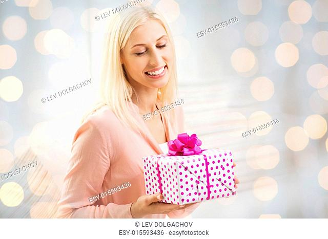 people, celebration, valentines day and birthday concept - smiling young woman with gift box over holidays lights background