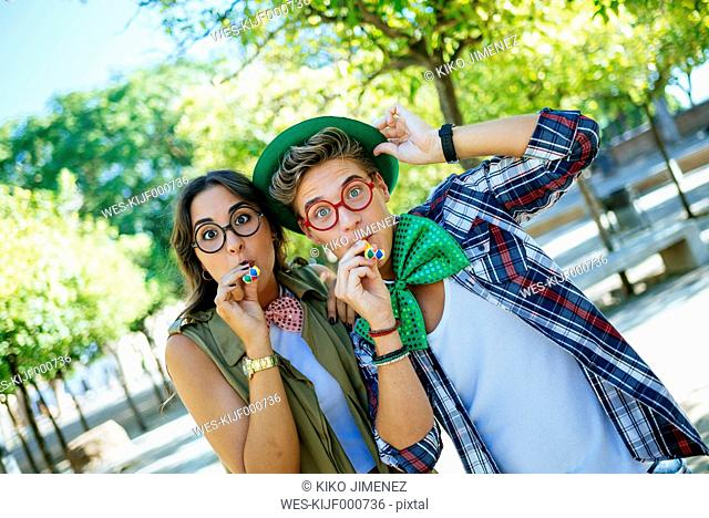 Young couple having fun with party blowers, joke glasses and caps