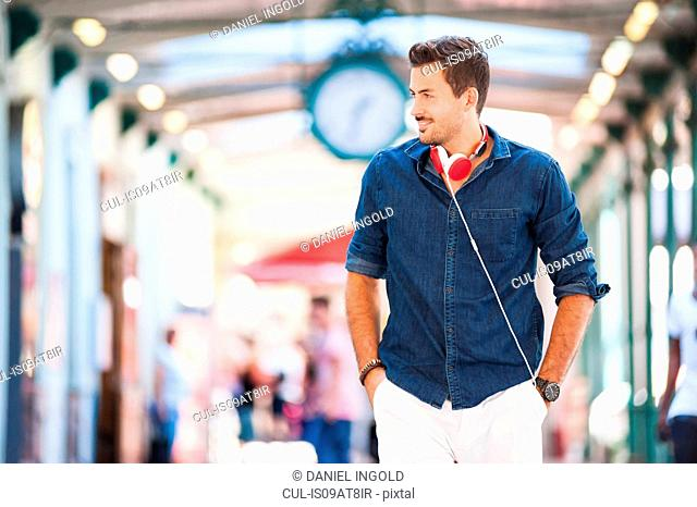Handsome young man wearing headphones strolling in station