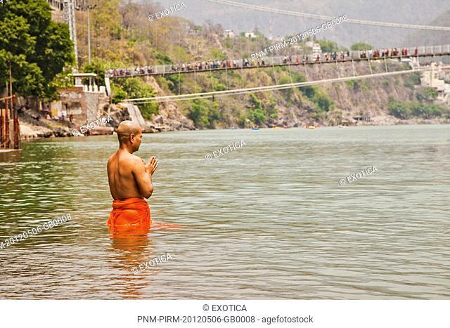Hindu monk praying in the sacred waters of holy Ganges River, Ram Jhula, Rishikesh, Uttarakhand, India