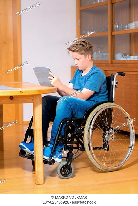 disabled boy in wheelchair doing homework and chatting in the internet