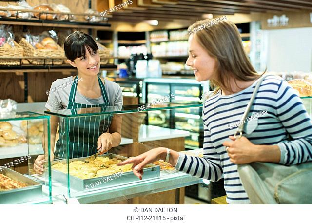 Clerk serving customer at deli counter in grocery store