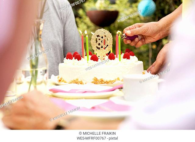 Hand lighting candles on 80th birtday cake