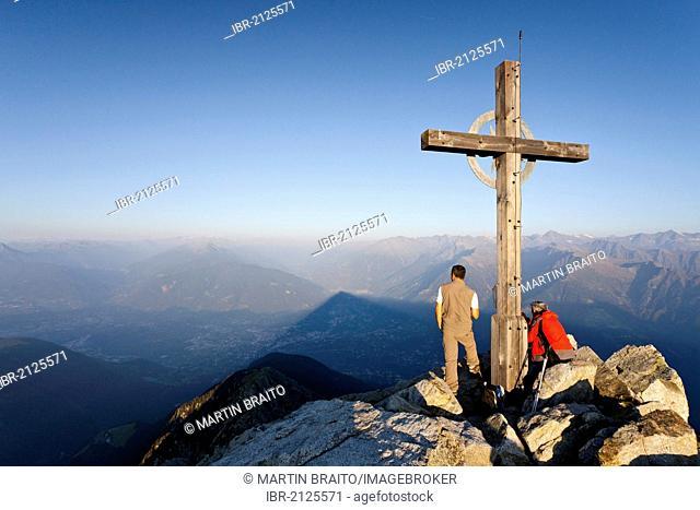 Climber at sunrise at the summit cross of Ifingers Mountain above Meran, Meran 2000, Alto Adige, Italy, Europe