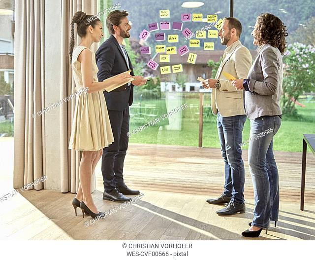 Colleagues discussing with sticky notes at the window