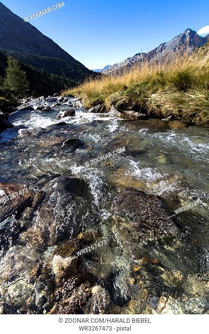Idyllischer Bergbach in den südtiroler Bergen im Herbst
