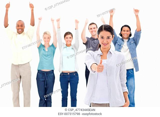 Close-up of a girl with people raising their arms and with their thumbs up in background