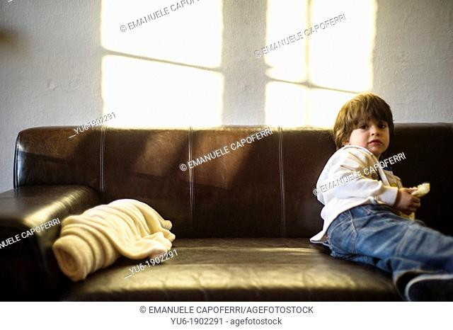 Sofa with rolled-up blanket and light from the window and child sitting