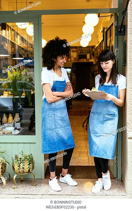 Two smiling women with clipboard standing in entrance door of a store
