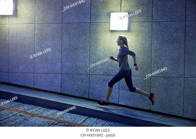 Female runner running ascending illuminated urban ramp