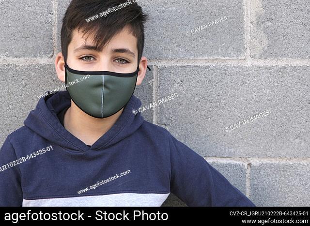 Green eyes boy wearing a green facemask . Coronavirus protection