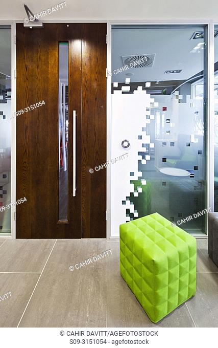 Contemporary styled modern office interior with bright green stool