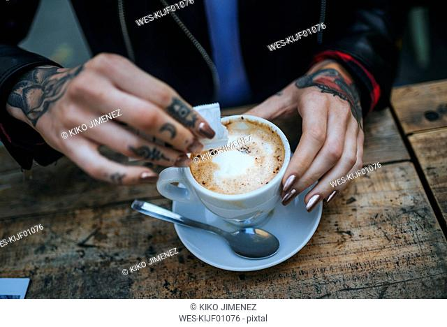 Woman's tattooed hands pouring sugar into cup of coffee, close-up