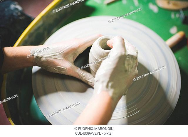High angle view of young womans hands shaping clay on pottery wheel