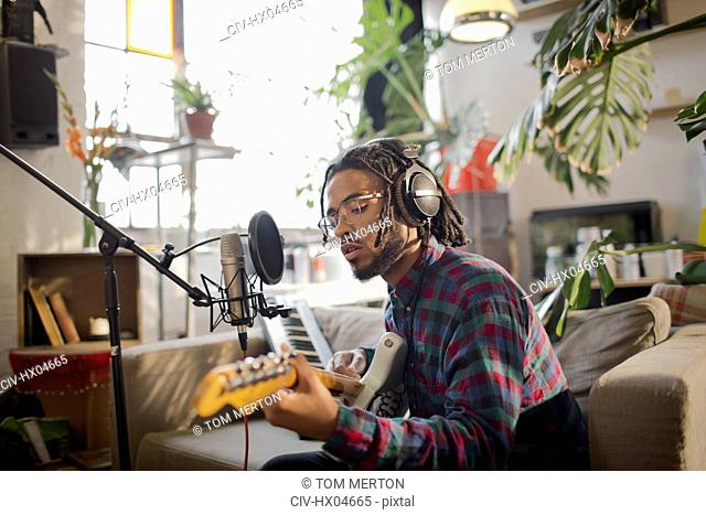 Young male musician recording music, playing guitar at microphone in apartment