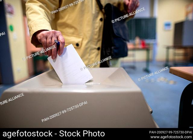 27 September 2020, North Rhine-Westphalia, Duesseldorf: A woman throws a ballot paper into a ballot box. The Marien-Schule in Düsseldorf is one of 315 voting...