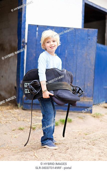 Boy carrying horse saddle