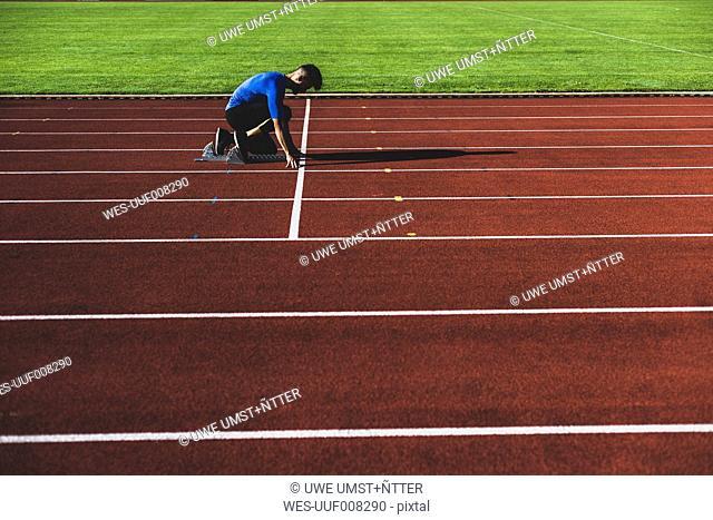 Runner on tartan track in starting position