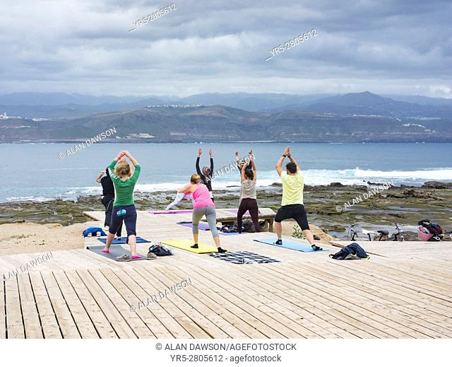 Yoga class overlooking Atlantic Ocean at El Confital near Las Canteras in Las Palmas, Gran Canaria, Canary Islands, Spain