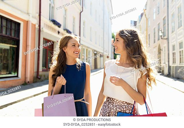 happy women with shopping bags on city street