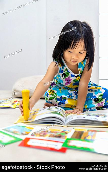Asian girl child reading interactive book in living room at home as home schooling while city lockdown because of covid-19 pandemic across the world