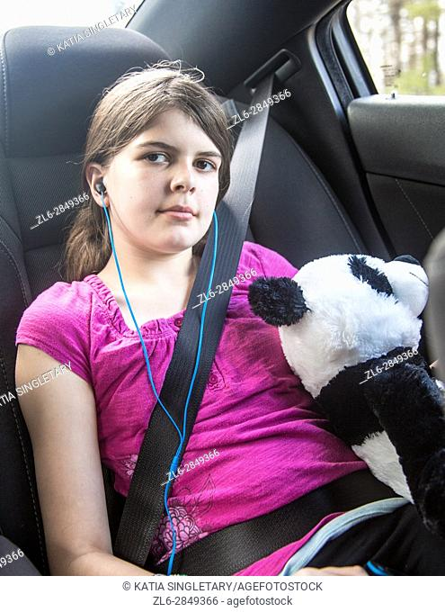 one caucasian preteen 11 years old in the car with her sit beat on and resting with oversized panda stuff animals