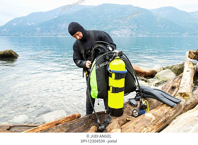 A scuba diver prepares his equipment before making a dive, Britannia Beach; Howe Sound, British Columbia, Canada