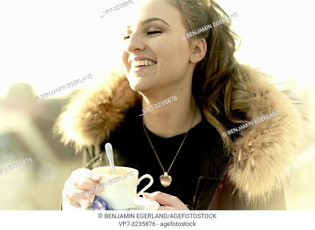 happy laughing woman holding porcelain coffee cup outdoors in city, wearing winter collar, in Munich, Germany