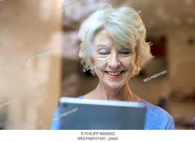 Portrait of smiling mature woman with behind windowpane looking at digital tablet