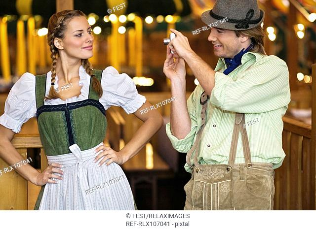 Young man taking photograph of girlfriend at Oktoberfest, Munich, Germany