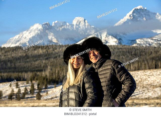 Caucasian couple smiling near mountains in winter