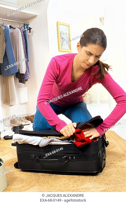Woman trying to close suitcase