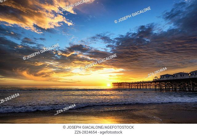 Vibrant, cloudy sunset view from Mission Beach with the Crystal Pier. San Diego, California