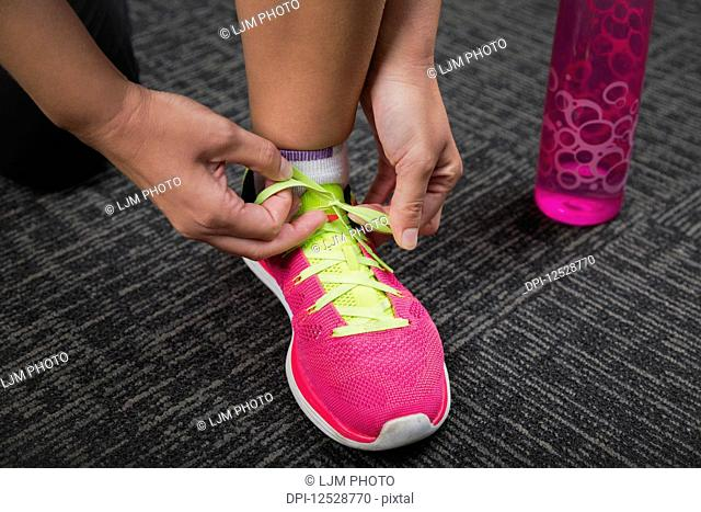 Woman tying a green shoelace on a pink running shoe while working out; Spruce Grove, Alberta, Canada