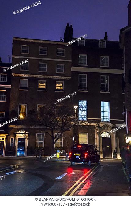 London cab passing by posh Georgian houses at night in Mayfair, London, England, UK