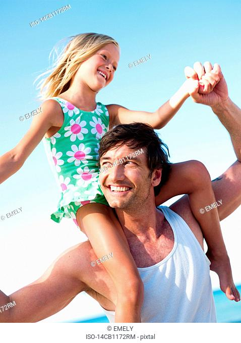 daughter and father playing on beach