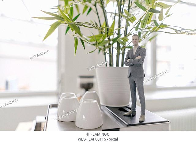 Miniature businessman figurine standing on coffee machine in office
