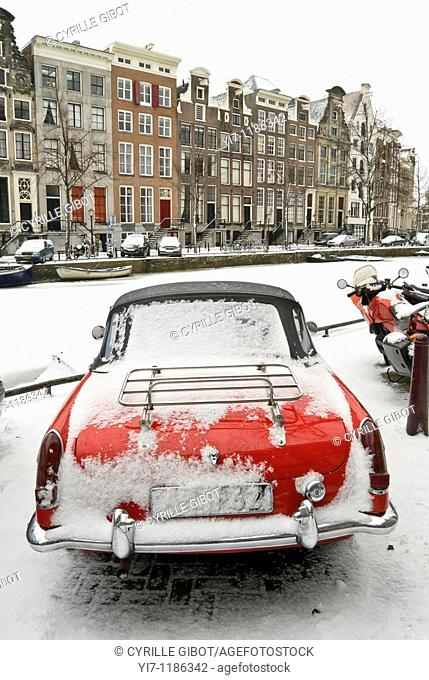 Red sports car by frozen Keizersgracht canal, Amsterdam, the Netherlands