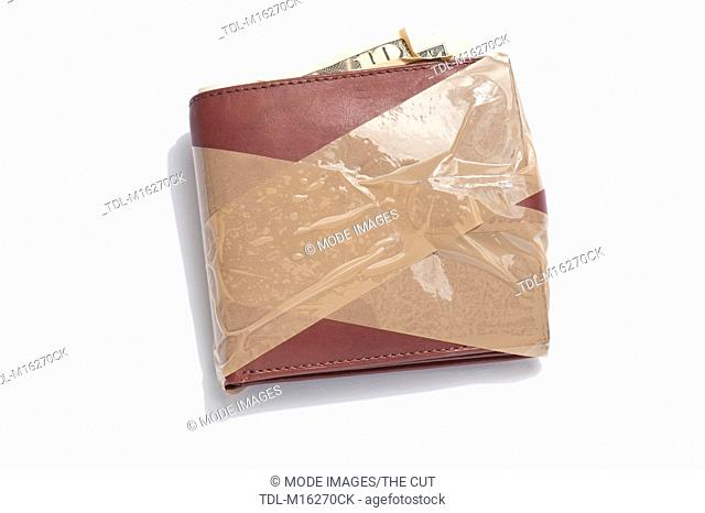 A brown leather wallet with brown tape around it
