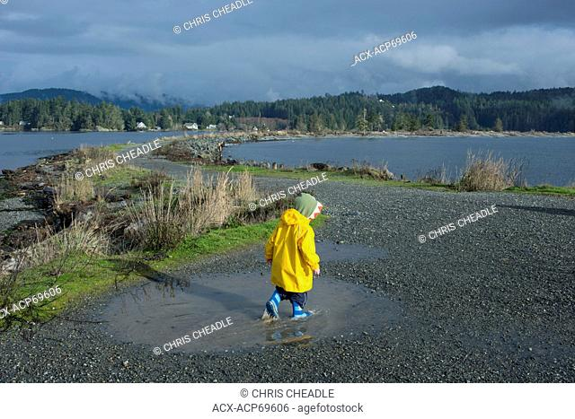 Child in puddle, Whiffin Spit Beach, part of Quimper Park in Sooke, British Columbia, Canada
