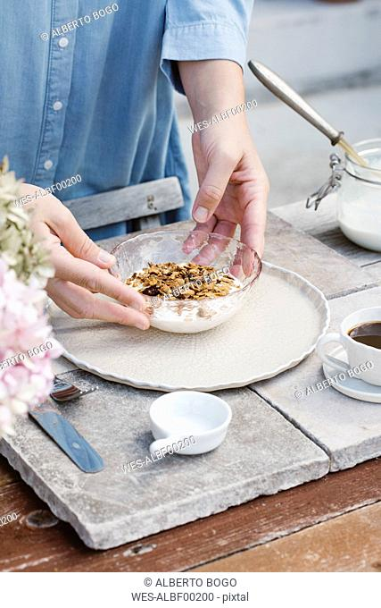 Italy, woman arranging bowl of granola on breakfast table, partial view