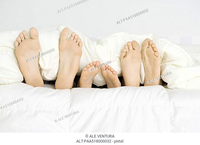 Child lying between parents under comforter, only bare feet sticking out