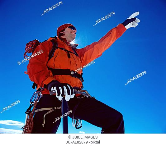 Low angle view of hiker in winter clothing pointing under blue sky