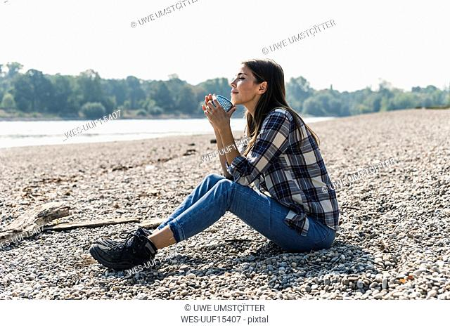 Relaxed young woman holding a mug sitting at the riverside