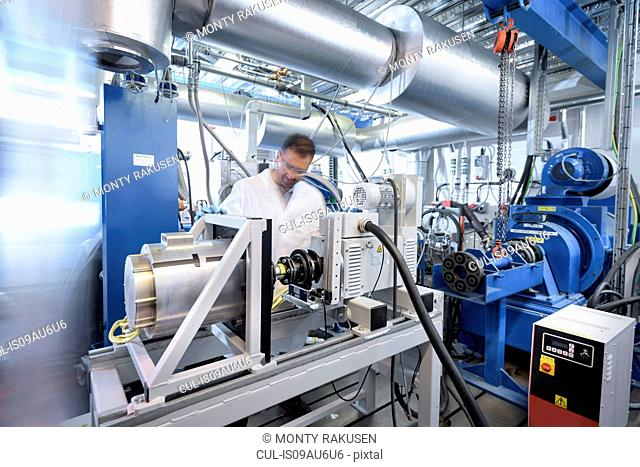 Scientists testing lithium car battery with electric motor car in battery research facility