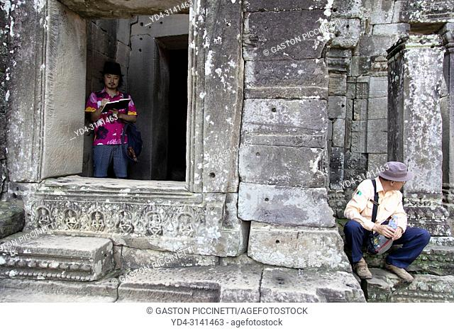 Tourist drawing one of the faces of the Bayon Temple in Angkor Thom, Angkor Temple Complex, Siem Reap, Cambodia, Southeast Asia