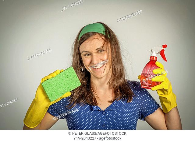 Young woman wearing rubber gloves and holding cleaning supplies